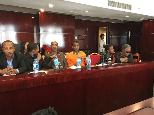 Pöydän takana istumassa kuusi tummaihoista ihmistä