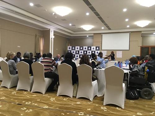 Selkäpäin oleva kuva ihmisistä istumassa valkoisissa korkeaselkäisissä tuoleissa seminaarissa