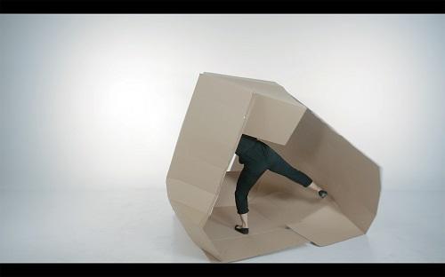 Ihmisenkokoisesta pahvilaatikosta näkyy mustapukuisen ihmisen alaosa.