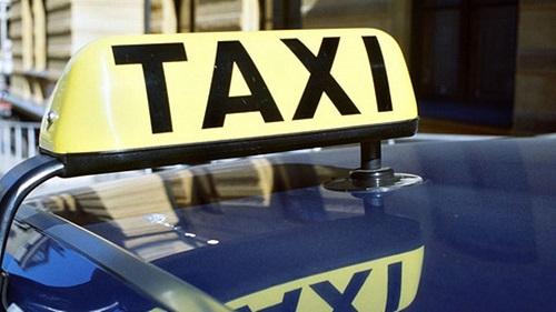 Taxi-kyltti taksn katolla keltaisella pohjalla