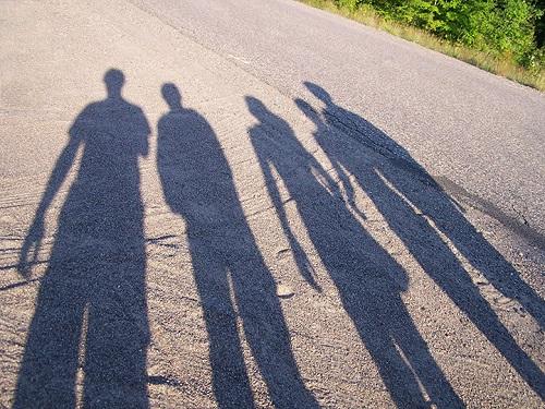 Neljä ihmisvarjoa aurinkoisella tiellä