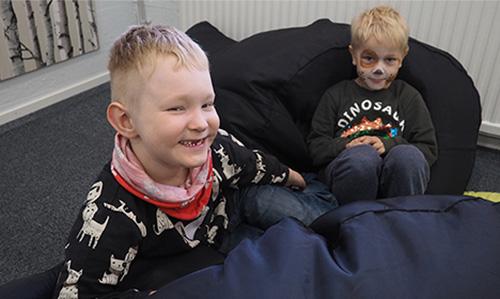 kaksi hymyilevää pikkupoikaa Harvinaiset-kurssilla, toisella koirameikki