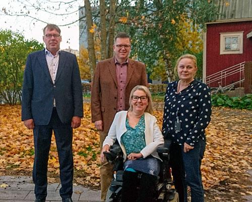 Syksyisessä ulkokuvassa seisoo kaksi taksiliiton miespuolista edustajaa sekä Riitta Saksanen Invalidiliitosta. Etualalla liiton lakimies Elina Nieminen istuu pyörtuolissa.