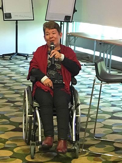 Haastateltava Marjo Mäkinen istuu pyörätuolissa ja puhuu mikrofoniin.