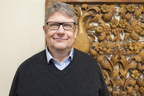 Kirkkoherra Markku Salminen katsoo kameraan. Taustalla taideteos.