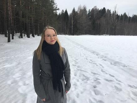 Nuori nainen mustassa kaulahuivissa ja harmaassa takissa seisoo lumisen pellon reunassa. Taustalla metsää.