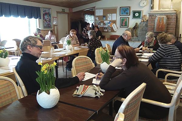 Yhdistysväkeä istuu pöydän ääressä tilassa, jossa on pääsiäiskoristelua.