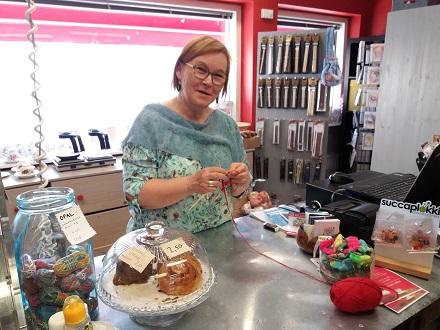 Neulekahvila Lentävän lapasen toinen omistaja Taina Schildt neuloo kahvilan tiskin takana.