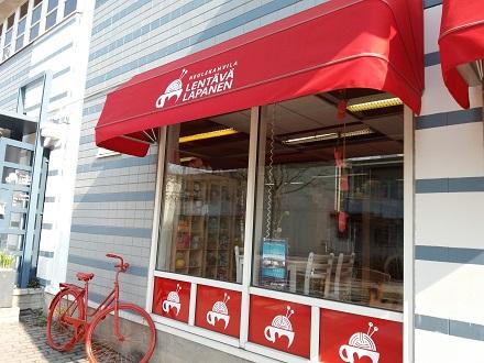 Neulekahvila Lentävän lapanen ulkoa: punainen polkupyörä ja markiisi