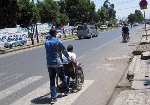 Addis Abeban kadulla toinen ihminen työntää toista pyörätuolissa