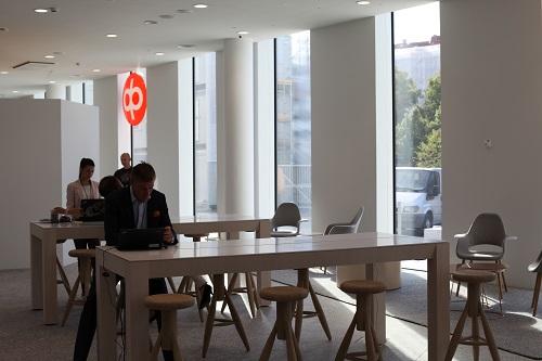 OP toimitiloissa valoisa tila jossa pöytiä ja tuoleja, ikkunat ulos, ikkunassa OP:n oranssi logo. Edummaisessa pöydässä istuu mies läppärin kanssa.