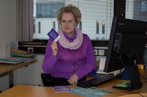 Lappeenrannan kaupungin asukasyhteyshenkilö Pia Pulliainen työpöytänsä ääressä, yllään violetti takki ja vaaleanpunainen huiv, kädessään violetti pieni YK:n vammaissopimus, pöydällä niitä vielä kaksi.
