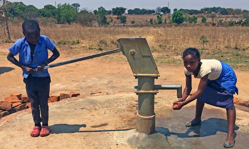Invalidiliiton lahjoittamalla kaivolla Sambian Kamuyngassa poika pumppaa vettä ja tyttö pesee käsiään