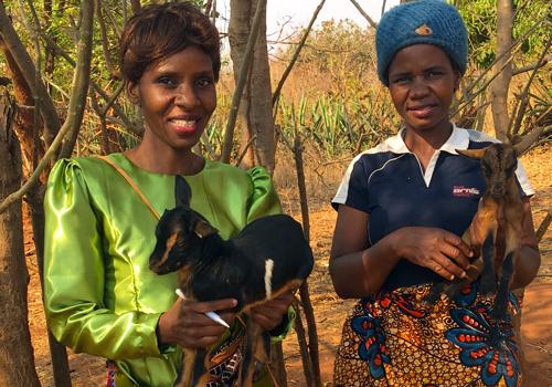 Sambian naisia pienet kilit sylissään. Taustalla puita.