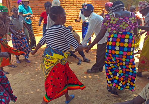 Sambialaisia tanssimassa piirissä, naisilla värikkäät hameet