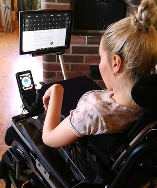 Vilma Kurran-Kuusela katselee pyörätuolissa tietokonetta.